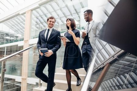 Photo pour Membres de l'équipe multiethnique financière en descendant les escaliers avec tablette et smartphone - image libre de droit