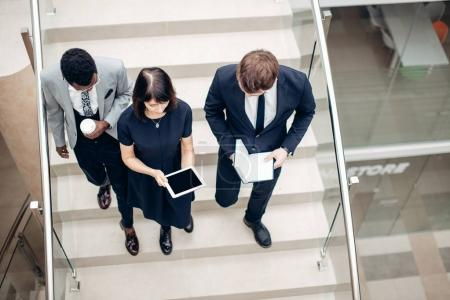 Photo for Team business people wear suit and walking down on step of stair and holding smartphone and tablet - Royalty Free Image