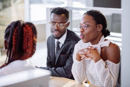 Photo pour Heureux couple africain et vendeur féminin s'asseoir à la table et faire un accord pour la vente de voiture - image libre de droit