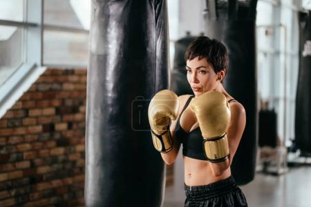 woman with athletic complection is striking blow.