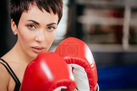 close up photo of attractive young woman with brown eyes in red boxing gloves