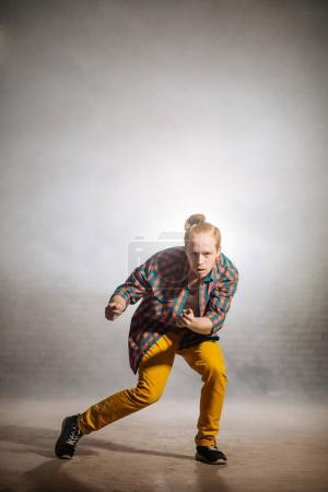 young male with checked shirt and yellow pantsbeckoning with the hands.