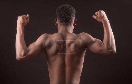 Afro sportsman flexing his muscles isolated on the black background