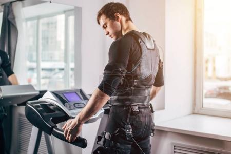Man in black suit for ems training running on treadmill at gym