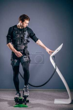 man training on stepper with electric muscle stimulation