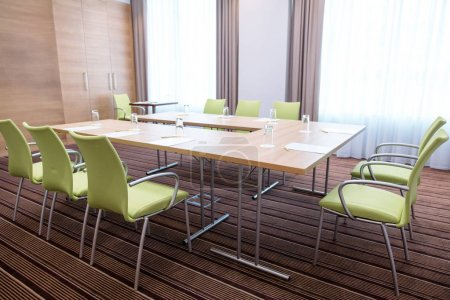 interior of light committee room furnished with modern table and green chairs
