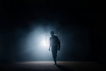 dark silhouette of slim man walking on the street at night