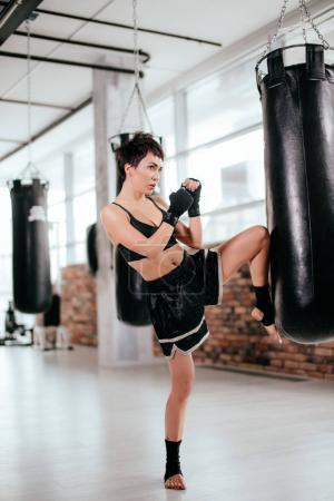 side view image of female muscular fighter with raised leg and clenched fists
