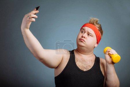 Photo pour Modèle masculin BigSize avec les lèvres de canard portant noir sportwear faire selfie tout en faisant fond gris exerciseon haltère - image libre de droit