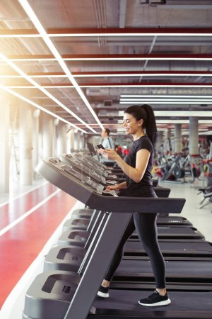 young Sportswoman using smartphone while jogging on treadmill