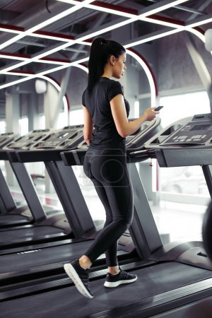 Sportswoman using smartphone for training workout app while jogging on treadmill