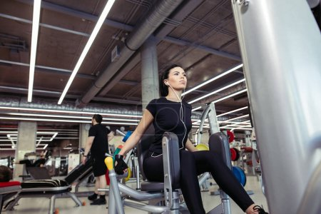 Adduction or abductor machine. girl exercising her legs in gym