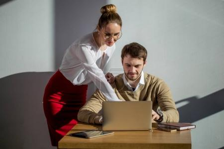 woman pointing at laptop with smile and discussing something with her coworker