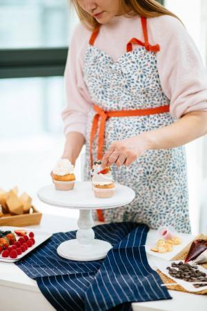 Photo pour Vue recadrée de femme décorant des cupcakes avec des baies sur le plateau de service - image libre de droit