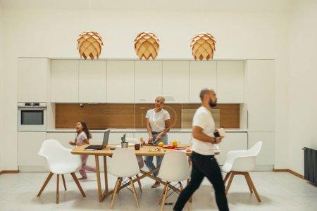 Photo pour Famille caucasienne en minimalisme intérieur cuisine blanche. Dîner de cuisine de la mère, jeu de l'enfant. Concept de foyer et de famille - image libre de droit