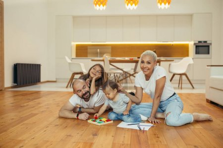 Photo for Smiling Family having fun together in living room of house. Mom, dad and two children on floor smiling, laughing, play. happy family concept - Royalty Free Image