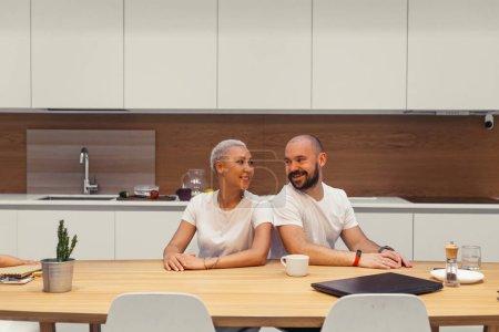 Photo pour Une famille attrayante, la femme et le mari s'assoient en kithcen et sourient, laught. Heureux ensemble à la maison. Couple en vêtements blancs, couleurs blanches intérieur. - image libre de droit