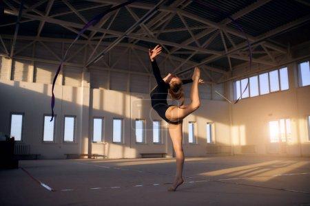 """Photo pour Femme souple et gracieuse se tenant sur la pointe des pieds, regardant vers le haut, s """"étirant vers l'extérieur, soulevant la jambe intensément en arrière, tendant les mains, concept de gymnastique rythmique - image libre de droit"""