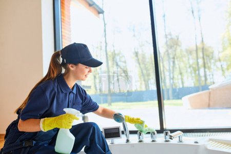 Photo for Young caucasian woman janitor cares about new house. Spring general clean up of cleaning service. Commercial cleaning company concept, Panoramic window background - Royalty Free Image