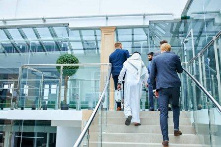 Photo pour Des Caucasiens de tuxedo ont invité des cheikhs à une réunion d'affaires. Des hommes d'affaires montent les escaliers du centre d'affaires - image libre de droit