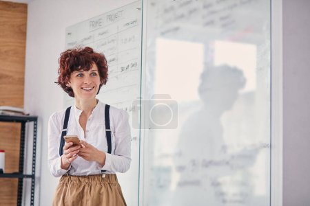 Photo for Beautiful caucasian woman using modern mobile phone during work in office, scheme board background - Royalty Free Image