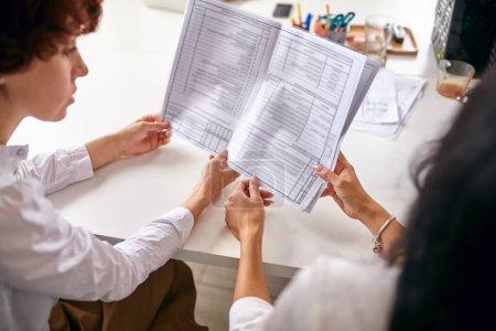 Photo pour Deux mains de femme tenant du papier lié au travail, processus de travail, discuter ensemble - image libre de droit