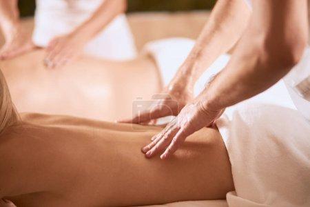 Photo pour Close up of strong hands of professional male masseur doing back massage to female client in spa center, beauty treatment concept - image libre de droit