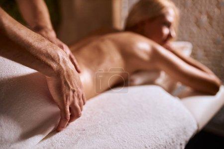 Photo pour Massothérapie des mains masculines utilisant l'huile d'arôme dans le centre de bien-être moderne, soins du corps, soins de la peau, concept de soins de santé, photo à angle bas - image libre de droit