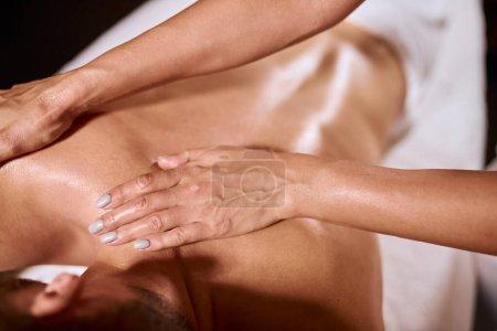 """Photo pour Gros plan des mains féminines faisant un massage aromatique sur le dos d'un homme, masseur professionnel gardant les paumes sur l """"épaule d'un jeune client, concept spa beauté santé - image libre de droit"""