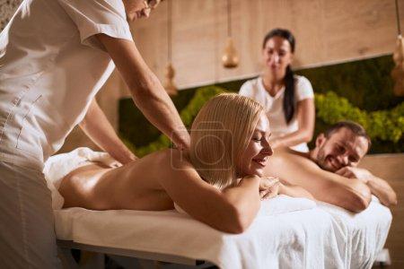 Photo pour Portrait de jeune couple lumineux allongé sur des serviettes blanches, recevant un massage des mains ensemble dans un salon de spa de beauté, souriant joyeusement, satisfait par le travail de masseurs professionnels, tourné d'en bas - image libre de droit