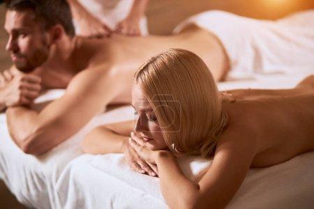 Photo pour Vue à grand angle d'un jeune couple passant du temps dans un salon de spa, couché sur des draps blancs, sous des serviettes souples, prêt à se faire masser les mains, photo d'intérieur, concept de relaxation - image libre de droit