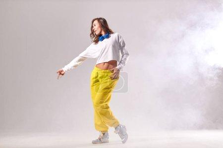 Photo pour Jolie formation active de danseuse dans une école de danse moderne sur scène pleine de fumée blanche, étirant la main latéralement, détournant les yeux, beauté, énergie de la mode et concept de fitness - image libre de droit