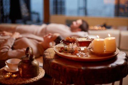 Photo pour Jeune homme et femme caucasien en robe de chambre, couché et en train de se reposer au spa dans un salon de beauté. Photo de thé et de bougies en couple couché derrière. Concept de détente et de mode de vie sain - image libre de droit