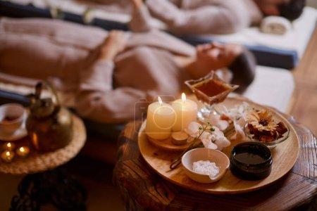 Photo pour Des hommes et des femmes de race blanche se détendent et boivent du thé couchés dans des lits spéciaux dans le salon de spa, portant des peignoirs, autour de bougies. - image libre de droit