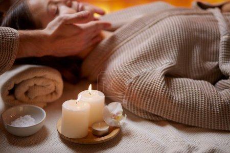 Photo pour Petite fille massant sur son visage dans un spa. Porter un peignoir et des bougies près d'elle. Soins de beauté - image libre de droit