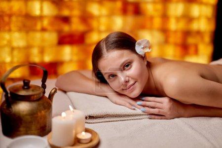 Photo pour Portrait de belle femme souriante allongée sur la table après ou avant la procédure de spa, se faire masser sur le dos, regarder la caméra et se détendre. Spa, soins de santé, concept de traitement - image libre de droit