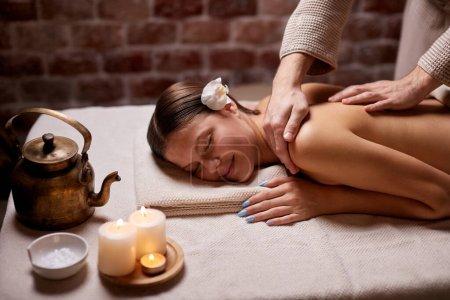 Photo pour Une belle caucasienne est venue au spa pour se faire traiter et masser sur son dos. S'allonger sur le dos nu - image libre de droit