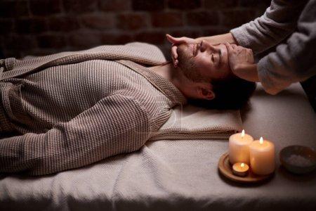 Photo pour Jeune homme en peignoir couché sur un bureau les yeux fermés se faisant masser le visage par un professionnel - image libre de droit