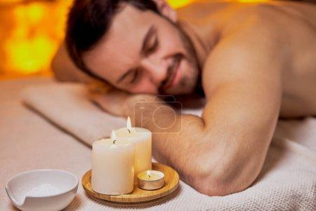 Photo pour Beau caucasien étendu après massage dans le salon de beauté, spa salon, peau nue. Jeune homme barbu relaxant, mur jaune en arrière-plan dans un spa - image libre de droit