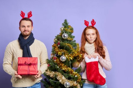 Photo for Beautiful couple having New Years photo session, posing over violet background, standing by beautifully decorated Christmas tree, keeping Santa stockings and Christmas gift, isolated, studio shot - Royalty Free Image