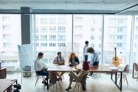 Photo pour Travaux de bureau en cours, conférences organisées par les employés de l'entreprise. 6 personnes dans un bureau lumineux avec de grandes fenêtres panoramiques. Ambiance de travail décontractée, détendue et amicale. - image libre de droit