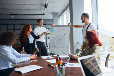 Photo pour Écouteurs d'un jeune homme d'affaires caucasien s'adressant à des partenaires d'affaires dans un bureau moderne - image libre de droit