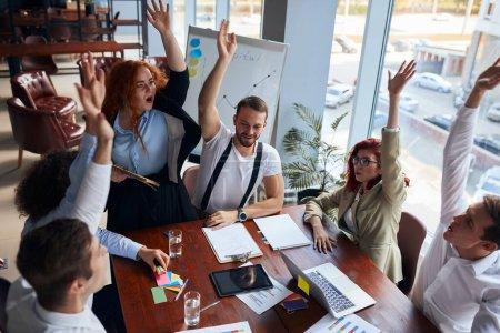Photo pour Une équipe joyeuse de jeunes collègues caucasiens s'est réunie pour conclure une réunion d'affaires couronnée de succès dans un bureau de conférence moderne, des papiers et des crayons colorés sur la table. Personnel de création - image libre de droit