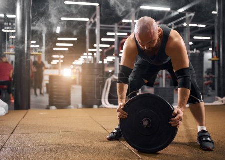 Photo for Brave brutal man trying to change heavy weight plate on barbell, trying hard, standing with wet head, makes efforts, sport and active lifestyle concept, side shot - Royalty Free Image