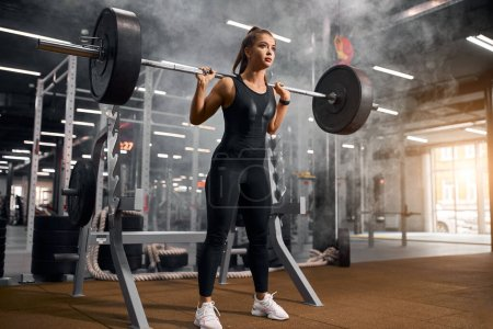 Photo for Strong female weightlifter standing in middle of big gym hall, keeping heavy barbell behind shoulders, looking away with confidence, getting power to start squatting, portrait, indoor shot - Royalty Free Image