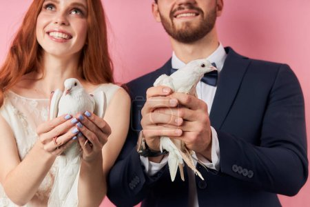 Photo for Charming lady and bearded caucasian man in tuxedo let pigeon out of hands, symbol of happy family life. Love, couple, relationships concept - Royalty Free Image
