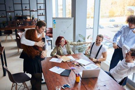 Photo pour Un groupe joyeux de gens d'affaires heureux après avoir gagné dans les gestes officiels de porter, serrez-vous les uns les autres. Partenariat réussi. Gens d'affaires, équipe d'affaires, concept de collaboration - image libre de droit