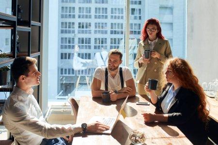 Photo pour Un groupe de collègues prenant un café, 2 hommes et 2 femmes bavardant. Bureau spacieux et spacieux avec fenêtres panoramiques, baigné de lumière du jour. Employés portant des tasses à café habillées de vêtements décontractés intelligents. - image libre de droit