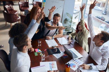 Photo pour Réussite du travail en équipe dans un bureau moderne, levée de la main après les avoir réunis au bureau, célébration d'une transaction commerciale - image libre de droit