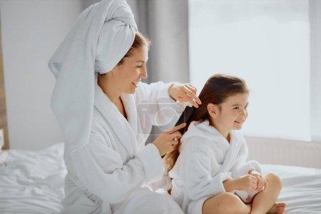 Photo pour Belle femme caucasienne assis peignage cheveux à belle fille, rangé après la douche dans une chambre blanche lumineuse. en peignoirs - image libre de droit